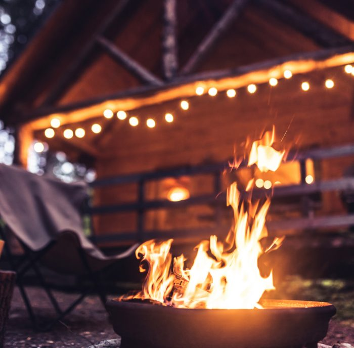 Late evening campfire in front of a wood log cabin